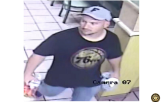 man wearing 76ers shirt and florida gators hat carrying sweatshirt in left hand