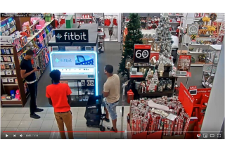 Three men standing in front of a fitbit display at kohl's