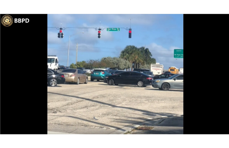 Cars stuck in traffic with a red traffic signal.