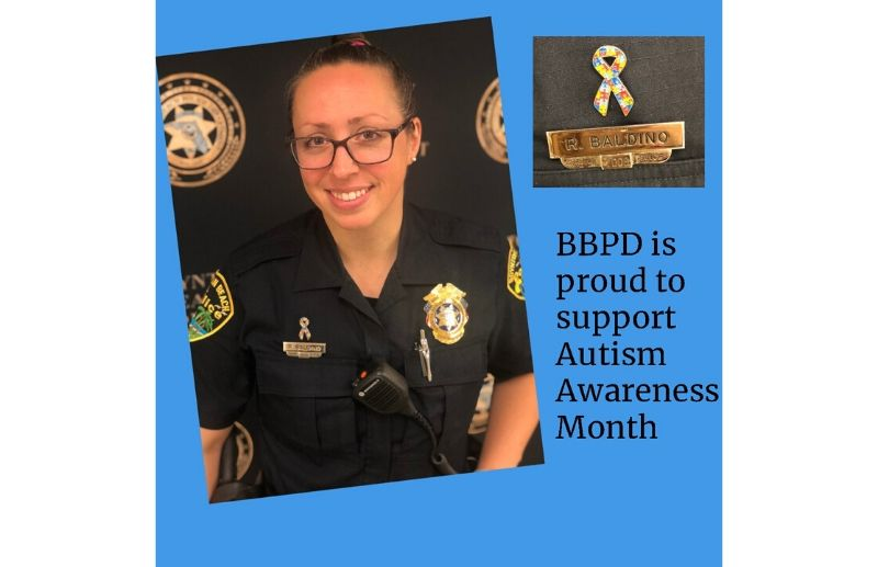 Police officer wearing a pin to support autism awareness month