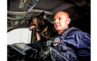 Dog leaning over a man's shoulder in a police car