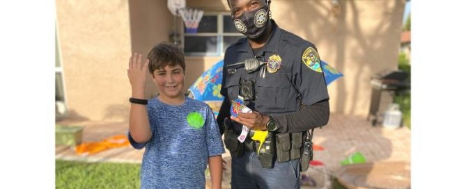 Police officer standing next to young male who is smiling and holding up his right arm to show bracelet that officer gave to him