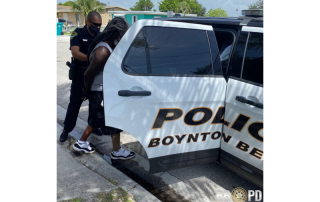 Police officer putting a man into the backseat of a police car.